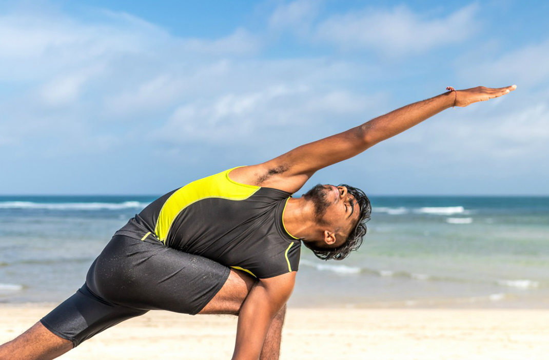 yoga on beach, how to work out while travel